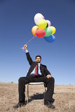 Businessman in outdoor holding balloons Royalty Free Stock Image
