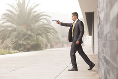 Businessman Outdoor. Powerful security businessman aiming a gun stock images