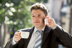 Businessman outdoors in coffee break holding cup talking on mobile phone smiling happy Stock Image