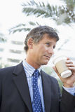 Businessman outdoors drinking coffee Royalty Free Stock Photo