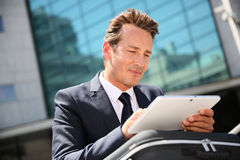 Businessman outdoors using tablet stock photo