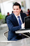 Businessman Outside. A young professional sitting in outdoor cafe with laptop computer Royalty Free Stock Images