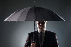 Businessman over black umbrella Royalty Free Stock Images