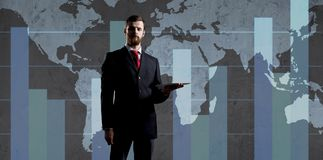 Businessman over dark background. World map background. Business, globalization, capitalism concept. Businessman with computer tablet standing over diagram royalty free stock image