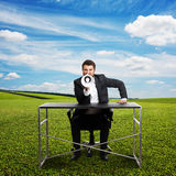 Businessman over green field and blue sky Royalty Free Stock Photos