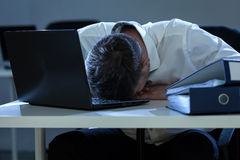 Businessman overwhelmed by problems at work. Middle aged businessman overwhelmed by problems at work Stock Photography