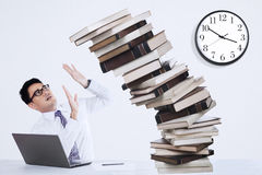 Businessman Overworked. With pile of books in the office Royalty Free Stock Image