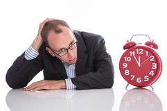 Businessman overworked with red clock isolated on white backgrou Stock Image