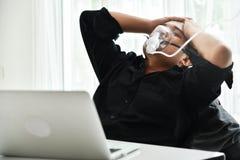 Businessman with oxygen mask having headache. Stressed Young Asian Businessman with oxygen mask having headache while he work overtime. Migraine stock photo
