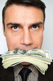 Businessman with pack of dollars in a mouth. Royalty Free Stock Images