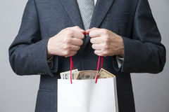 Businessman with package full of money in the hands of Royalty Free Stock Photos