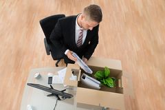 Businessman Packing Belongings In Cardboard Box. At The Desk Royalty Free Stock Photos