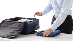 Businessman packing clothes into travel bag. Business, trip, luggage and people - close up of businessman packing clothes into travel bag stock video footage
