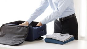 Businessman packing clothes into travel bag stock footage