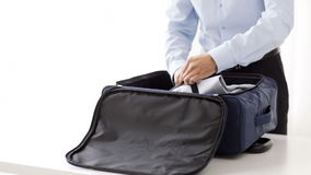 Businessman packing clothes into travel bag. Business, trip, luggage and people - close up of businessman packing clothes into travel bag stock footage