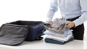 Businessman packing clothes into travel bag stock video footage