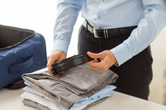 Businessman packing clothes into travel bag Stock Image