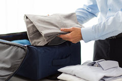 Businessman packing clothes into travel bag. Business, trip, luggage and people concept - close up of businessman packing clothes into travel bag Stock Images
