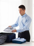 Businessman packing clothes into travel bag Royalty Free Stock Images