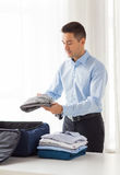 Businessman packing clothes into travel bag Stock Photo