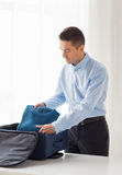 Businessman packing clothes into travel bag Royalty Free Stock Photography