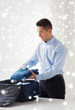 Businessman packing clothes into travel bag Stock Photography