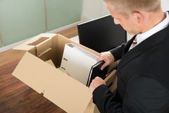 Businessman packing files in cardboard box Royalty Free Stock Images