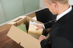 Businessman packing files in cardboard box Royalty Free Stock Photography