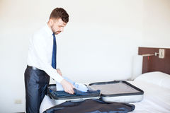 Businessman packing his bags in a hotel stock photo