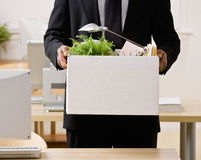 Businessman packing personal desk items in box Stock Photography