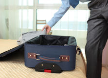 Businessman packing a suitcase Stock Photos