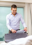 Businessman packing things in suitcase Stock Images