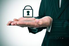 Businessman and padlock icon. A man wearing a suit with an icon of a padlock on his hands Royalty Free Stock Images