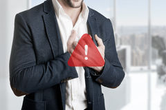 Businessman in Pain. Man having a pain in the heart area, with a warning sign over him Stock Photography