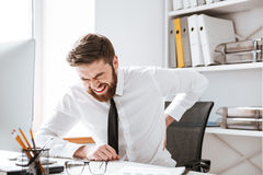 Businessman with painful feelings holding his back. Royalty Free Stock Images