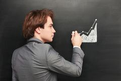 Businessman painting graph on chalkboard Royalty Free Stock Images