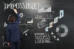 Businessman painting graphs on chalkboard Stock Photos