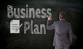 Businessman paints business plan on blackboard concept stock image