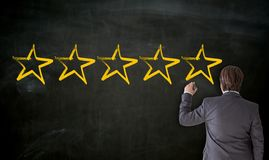 Businessman paints with chalk five stars on blackboard royalty free stock images