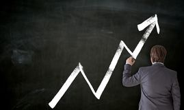 Businessman paints with chalk graph on blackboard stock photography