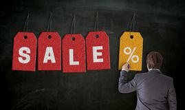 Businessman paints with chalk SALE concept on blackboard stock photography