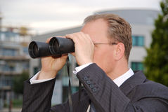 Businessman with a pair of binoculars Royalty Free Stock Photos