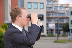 Businessman with a pair of binoculars Stock Images