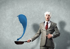 Businessman with pan Stock Images