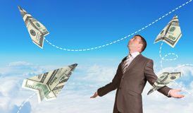 Businessman with paper airplanes made of hundred Stock Photo