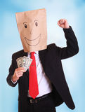 Businessman with a paper bag with smile on head holds money in his hand royalty free stock images