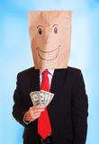 Businessman with a paper bag with smile on head holds money in his hand stock image
