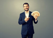 Businessman with paper money over dark Stock Photo