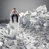 Businessman with paper sheet anywhere. Buried by bureaucracy concept. Royalty Free Stock Image