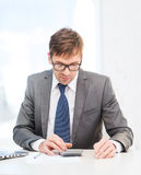 Businessman with papers and calculator Royalty Free Stock Images